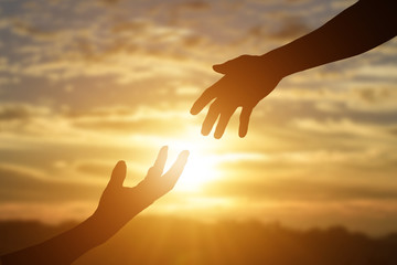 Silhouette of giving a helping hand, hope and support each other over sunset background. Fotomurales