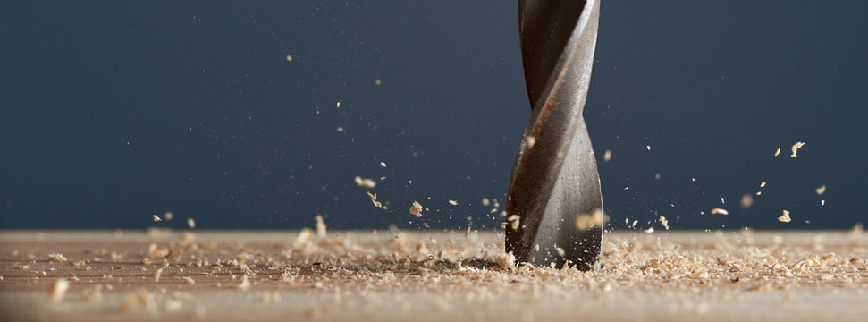Wood drill bit in the blur with shaving on a gray background. Photo with copy space.