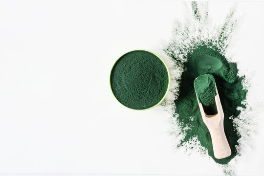 Organic green spirulina powder top view on white background. Super foods, food supplement source of protein and beta carotene.