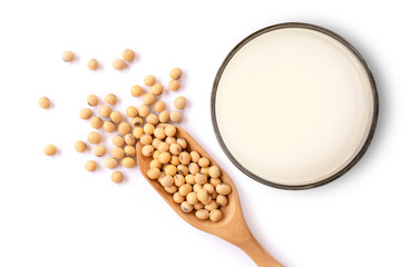 Closeup soy beans in wooden bowl and glass of soy milk isolated on white background. Top view. Flat lay.