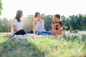 Mother and two daughters make picnic in a park at sunset in summer