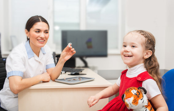 Little girl patient is very pleased that she will now hear sounds of surrounding world using hearing aid. Hearing clinic