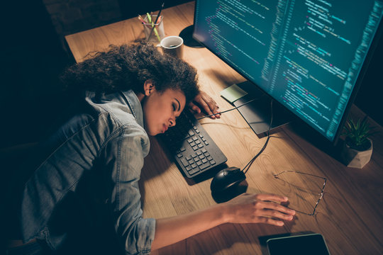 High angle view photo of pretty dark skin business lady fell asleep near monitor work overtime deadline terms specs telephone lying table wear casual shirt sit night office indoors