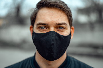 Portrait man in medical mask. Young man stands on light background and looking at camera. Wall mural