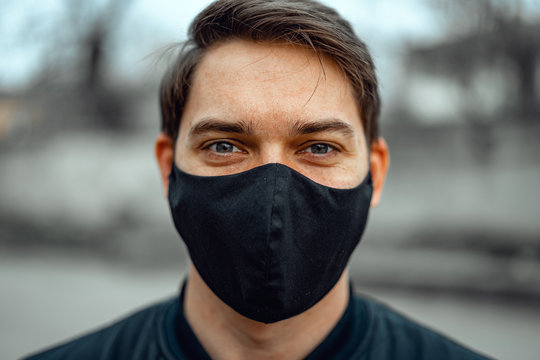 Portrait man in medical mask. Young man stands on light background and looking at camera.
