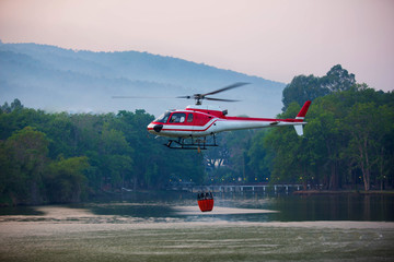 The helicopter is drawing water from the reservoir and will be watered to extinguish the burning forest in the mountains.