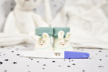 Green and white baby booties and pregnancy test. new life concept. new parents.