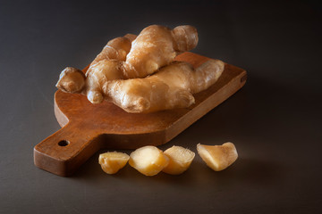 Sliced ginger root on a wooden background. Close-up. Low key