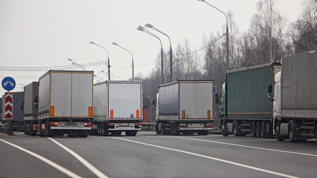 Closed state border, semi trucks queue on anti viral quarantine control point at spring day, internation logistics trouble illustration concept