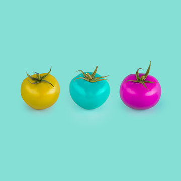 Three tomatos with strange color on blue background. Concept of GM food.