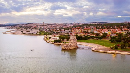 Wall Mural - Lisbon, Portugal. Aerial view of Belem Tower in Lisbon, Portugal during the cloudy day. Time-lapse of famous buildings with a crowd of tourists