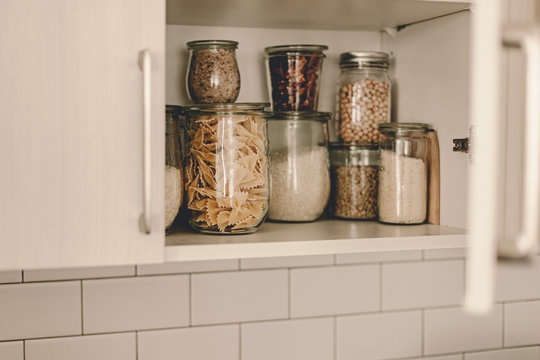 Kitchen storage organization. Zero waste, plastic free. Pasta, grains in glass jars. Organic food. Home cooking. Pantry food cabinet. Nutrition food. Glass containers. Food preparation. Stay home.