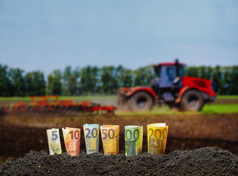 Euro banknotes from 5 to 200 grow from the ground. Tractor cultivating field at spring. Agriculture and money concept