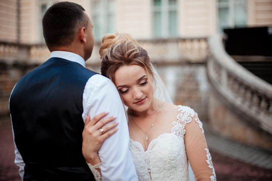 The bride and groom walk together in the park. Charming bride in a white dress, the groom is dressed in a dark elegant suit.