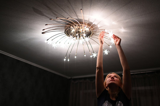 Evgenia Pivovarova changes light bulbs in a chandelier during self-isolation at home in the southern city of Rostov-on-Don
