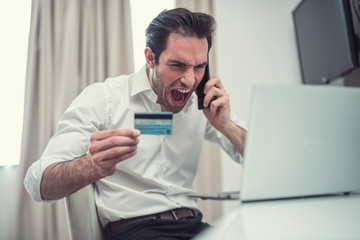 Handsome businessman are furious with credit card and mobile. Wall mural