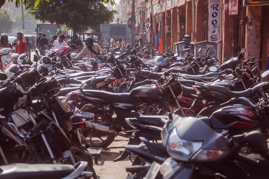 JAIPUR, INDIA, 2.12.2016: Huge amount of motorbikes and scooters parked on a street in Jaipur. People walking past. Motorcycle parking.