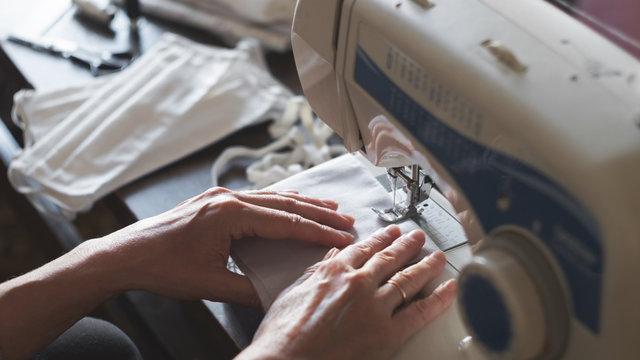 Woman sews protective antivirus masks at home on a sewing machine