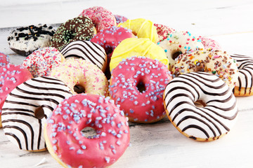 donuts in different glazes with chocolate, sprinkles and stripes