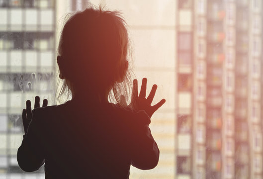 Girl looks out the window against the background of apartment building concept stayathome