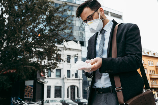 Elegant business man with protective mask putting gloves on his hands to protect himself from dangerous virus infection.