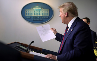 U.S. President Donald Trump holds a letter from the White House physician reporting that the president has tested negative a second time for coronavirus disease in Washington