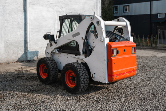 White skid steer loader at a construction site waiting of work. Industrial machinery. Industry.