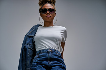 Confident lady in sunglasses in white t-shirt in jeans with denim jacket posing on camera with chest forward and holds hands behind her back. Fashion concept