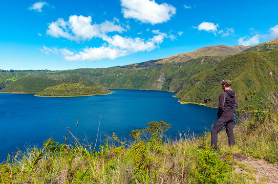Unrecognizable Caucasian male tourist looking over the volcanic Cuicocha crater lagoon on a sunny summer day, Otavalo, north of Quito, Ecuador.
