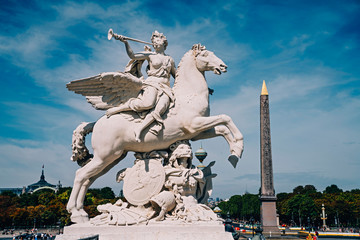 Angel on horse statue with Luxor Egyptian obelisk in the background at the Place de la Concorde in Paris, France