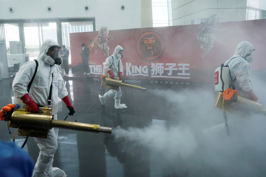 Volunteers from the Blue Sky Rescue team disinfect at the Qintai Grand Theatre in Wuhan