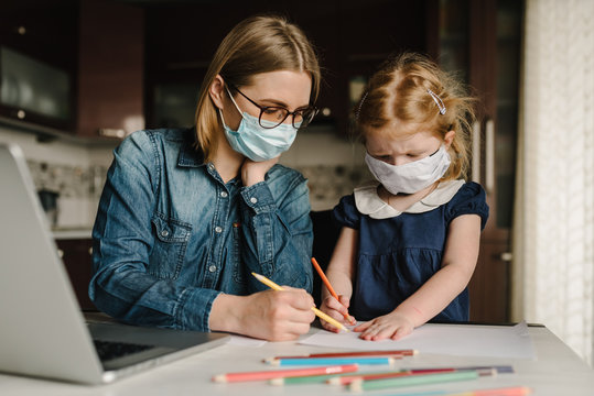 Coronavirus. Mom and daughter wearing protective mask in quarantine. Stay at home, woman working on laptop while taking care of baby. Freelance work. Child make noise, playing and disturb mom.