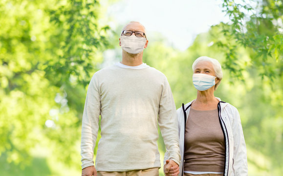 health, quarantine and pandemic concept - senior couple wearing protective medical mask for protection from virus holding hands outdoors over green natural background