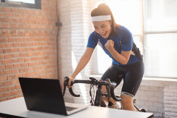 Asian woman cyclist. She is exercising in the house. By cycling on the trainer And playing online bike games, she is glad to succeed.