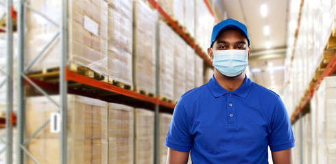 health protection, safety and pandemic concept - happy indian delivery man in blue uniform wearing face protective medical mask for protection from virus over warehouse background Wall mural