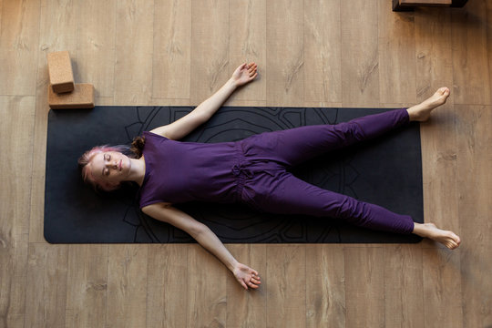 Modern girl is doing home yoga exercise. Lying on  floor in asana savasana. Zen relaxation after sports. Top view. Sleeps resting. Stretching Fitness Studio Online yogini trainer. silence meditation