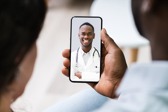 Couple Videoconferencing With Doctor On Mobile Phone