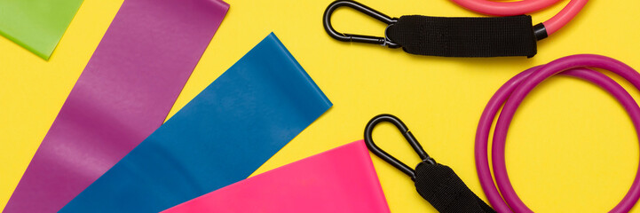 Expanders and elastic bands for fitness with different degrees of load on a yellow background....