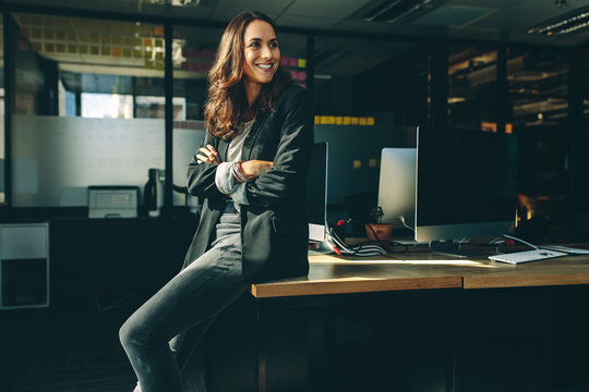 Smiling businesswoman sitting on her desk