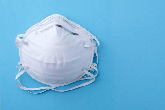 Two face masks or respirators 3M with copy space on blue background . Concept of virus protection