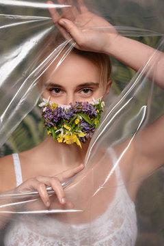 Quarantined woman wearing a coronavirus wears a protective mask of flowers