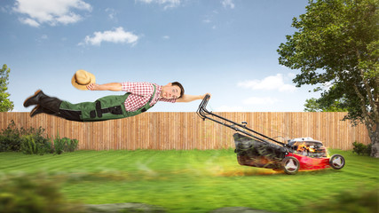 Funny gardener with a powerful lawn mower Wall mural