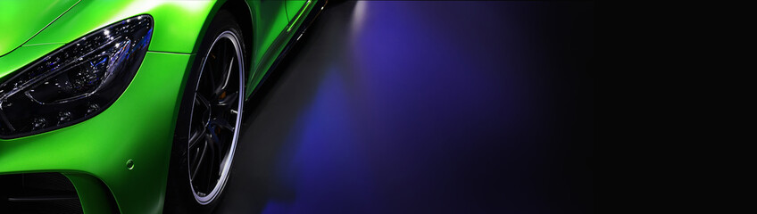 Wall Mural - Front headlights of green modern car on black background