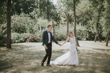 Portrait of a lovely bride and groom embrace, kiss and hug each other. Couple in love in the bosom of nature . Handsome groom and beautiful blonde bride posing in the forest. Modern dress and suit