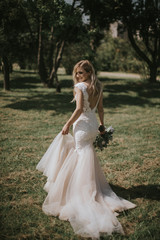 Portrait of a wedding bride walking in a white modern hipster dress. Caucasian blonde bride in a vintage dress in the forest on sunset. Attractive lady posing with a bouquet of flowers