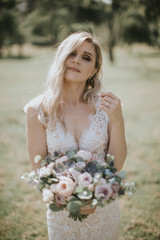 Portrait of a wedding bride posing in a white hipster style dress with flowers in her hands. Caucasian blonde bride in a vintage dress in the forest on sunset. Attractive bride shooting