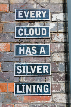 "Signs on a brick wall saying ""Every cloud has a silver lining"""
