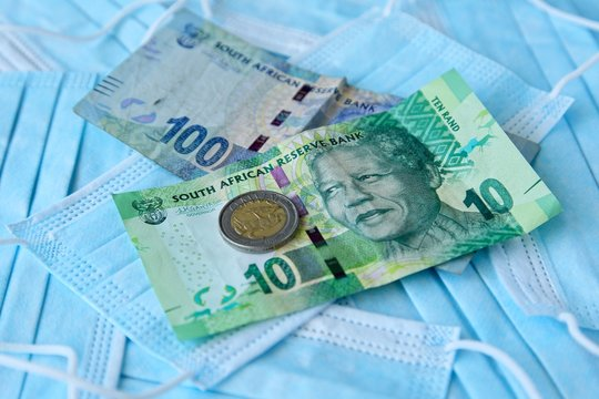 South African money on top of medical face masks. Cost of preventing infectious viruses such as the coronavirus (Covid-19) concept image.