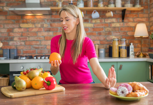 Woman choosing to eat healthy and fresh fruits versus bad unhealthy ones