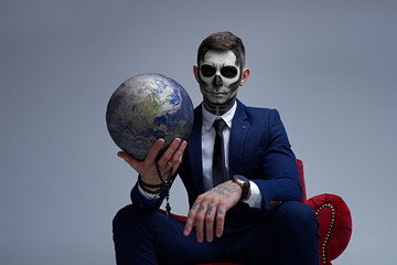 Satan holds the world in his hands. Planet earth in the hands of death. Man With Body Art Skeleton. Portrait of a skeleton in a suit looking at the camera.